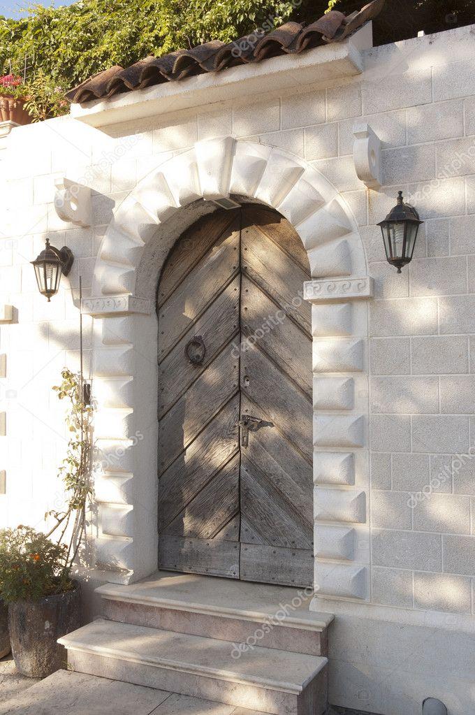 Fachada de piedra con puertas de madera viejas y luces de for Puertas de calle de madera