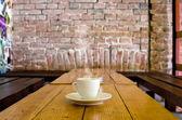 在一家酒吧的木桌上的咖啡杯 — 图库照片
