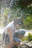 Jong meisje in de buurt van een fontein — Stockfoto