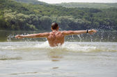 Young strong man cavorting in the water — Stock Photo