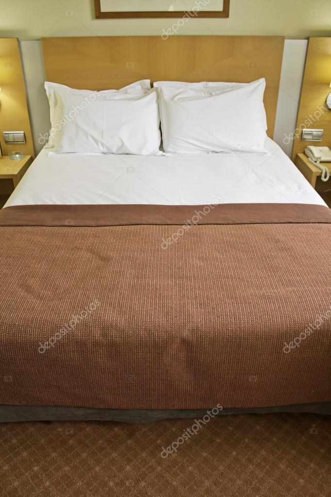 Hotel bed and bedside tables with red bedspread, decoration — Stock Photo #15776963