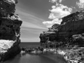 Australia. Great Ocean Road. Flaky limestone with rocky lake, monochrome. — Stock Photo