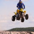 Vadim Vasuhin in jump with springboard on quadrocycle during extreme motorcross racing August 26, 2007 in Nadym, Russia. — Stock Photo