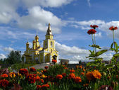 Nadym. The Orthodox temple with flowerses on background blue sky. — Stock Photo