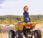 Krásná blondýnka na sportovní quadrocycle na pozadí přírody. — Stock fotografie