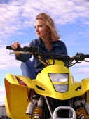Belle blonde sur sport quadrocycle sur fond de ciel bleu. — Photo