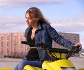 Beautiful blonde on sport quadrocycle on background of the city Nadym. — Stock Photo