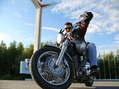 Classical biker Klimenko Oleg in black spectacles sits on chopper. Nadym, Russia. — Stock Photo