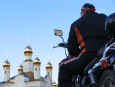 Classical biker looks at church temple. Nadym, Russia. — Stock Photo