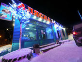 New Year - a holiday in Nadym, Russia - February 25, 2013. Festive street decorations. Beautifully illuminated building and trees. Far north, Nadym. — Stock Photo