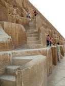 Egyptian step pyramid closeup. Felled level in the pyramid. Strangers: men, women and children - the tourists go on a pyramid. — Stock Photo