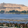 Stock Photo: Africa, Egypt. Pier on bank of Nile in Aswan, on background of ancient sites in Egypt.