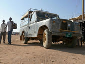 Two strangers - Nubians going past the jeep in Wadi - Halfa, Sudan - November 19, 2008. Old jeep. Architectural building. — Foto Stock