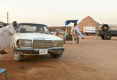 Strange men Nubians. Unknown man with a donkey cart, controls in Wadi - Halfa, Sudan - November 19, 2008. City street. Parked cars. — Stock Photo