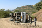 ROBY, ETHIOPIA - NOVEMBER 23, 2008: Crash. Truck flipped in the mountains in Roby, Ethiopia - November 23, 2008. Strangers near a truck. — Stock Photo