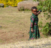 JIGA, ETHIOPIA - NOVEMBER 24, 2008: Field with yellow flowers in Jiga, Ethiopia - November 24, 2008. Stranger smiling African child - a girl holding a stick in his hand. — Stock Photo