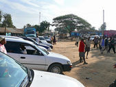 MOYALE, ETHIOPIA - NOVEMBER 27, 2008: The village on the border between Ethiopia and Kenya. Houses. Cars parked. Unfamiliar villagers go about their business. — Stock Photo