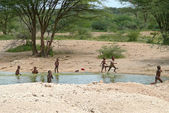 ISIOLO, KENYA - 28 NOVEMBER 2008: Unknown small Kenyan children bathe in the river in Isiolo, Kenya - 28 November 2008. River and trees around. — Stock Photo