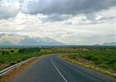 The cloudy sky. The road. Mountains in the distance. Tanzania, A — Stock Photo