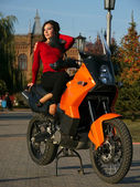 Beautiful young brunette woman on a motorcycle. — Stockfoto