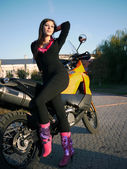 Beautiful young brunette on the background of a motorcycle in th — Stock Photo