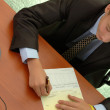 Teenager - businessman signs document. — Stockfoto