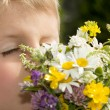 Young Boy Smelling Bouquet of Wildflowers — Stock Photo