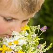 Stock Photo: Young Boy Smelling Bouquet of Wildflowers