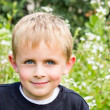Stock Photo: Young Boy Sitting in the Garden