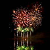 Bursts of Red, Orange and Green Fireworks — Stock Photo