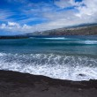 Sandy black volcanic beach in Puerto de la Cruz with nice clouds in the sky, Tenerife - Stock Photo