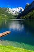 Wooden jetty for tourist boats on alpine lake with crystal clear green water — Stock Photo