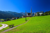 Mountain road on green meadow in alpine village with church in the distance — Stock Photo