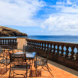 Sea view and metal chairs with glass table on restaurant terrace on sunny summer day , Madeira island, Portugal — Stock Photo #36029555