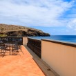 Sea view and metal chairs with glass table on restaurant terrace on sunny summer day , Madeira island, Portugal — Stock Photo #36029561