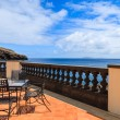 Sea view and metal chairs with glass table on restaurant terrace on sunny summer day , Madeira island, Portugal — Stock Photo #36029563