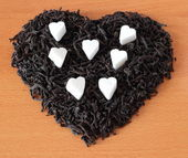 Black tea dry lined heart-shaped with pieces of sugar — Stock Photo