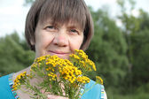 Middle-aged woman with medicinal flowers of tansy — Stock Photo