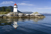The nature of summer Norway. Reflections in fine pure water. Beacon on rocky coast — Zdjęcie stockowe