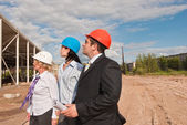 Director with subordinates on construction site of shopping cent — Stock Photo