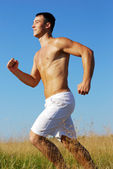 Athletic man running in outdoor scene — Stock Photo