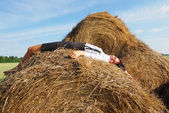 Woman on hay bale in summer field — Stock Photo