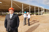 Director with subordinates on construction site — Stock Photo