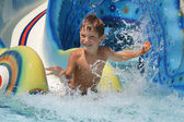 Outdoor portrait of young smiling child having fun in aquapark — Stockfoto