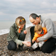 Young happy family on beach — Stock Photo #12605114
