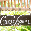 Come again phrase on wooden board - Stock Photo
