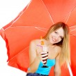 Attractive girl with glass of juice under red umbrella over whit — Stock Photo #12605956