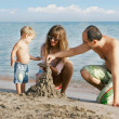 Young happy family on beach - Stock Photo