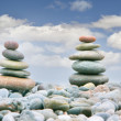 Two stacks of stones over sky background - Stock Photo