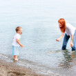 Mother and son playing in water on beach — Stock Photo #12607698